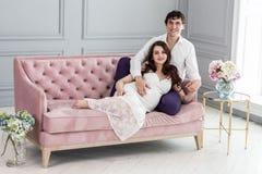 Potomstwo para oczekuje dziecka siedzi wpólnie indoors fotografia royalty free