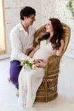 Potomstwo para oczekuje dziecka siedzi wpólnie indoors obrazy stock