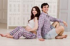 Potomstwo para oczekuje dziecka siedzi wpólnie indoors obrazy royalty free