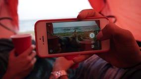 Potomstwo para odpoczynek w czerwonym namiocie blisko morza Kobieta chwyta ingher smartphone i robić fotografia dwa filiżanki zdjęcie wideo