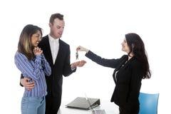 Potomstwo para otrzymywa klucze od żeńskiego agenta nieruchomości Fotografia Stock