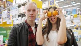 Potomstwo para przy hypermarket Dziewczyna patrzeje kamer? w supermarkecie robi ?miesznemu grymasowi z tangerines zbiory