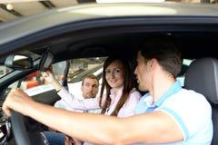 Potomstwo para radzi sprzedawcą przy przedstawicielstwem firmy samochodowej Zdjęcia Stock