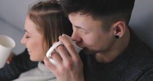 Potomstwo para relaksuje wpólnie w domu siedzieć na kanapie z herbatą zdjęcie wideo