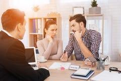 Potomstwo para robi decyzjom co do zakupu domowy obsiadanie w biurze nieruchomości agencja zdjęcia royalty free