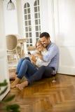 Potomstwo para siedzi na podłogowym, pijący czerwonego wina i kobiety usin Obraz Stock
