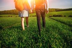 Potomstwo para spaceruje przez greenfield Kobieta i mężczyzna obrazy royalty free