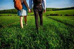 Potomstwo para spaceruje przez greenfield Kobieta i mężczyzna zdjęcie stock