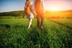 Potomstwo para spaceruje przez greenfield Kobieta i mężczyzna zdjęcie royalty free