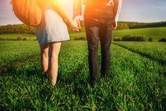Potomstwo para spaceruje przez greenfield Kobieta i mężczyzna trzymamy each inny rękami fotografia royalty free