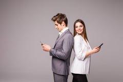 Potomstwo para używa mądrze telefony i ono uśmiecha się popierać na szarym tle podczas gdy trwanie z powrotem zdjęcia stock