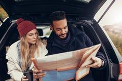 Potomstwo para używa mapę na wycieczce samochodowej Zdjęcie Stock