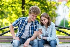 Potomstwo para w lecie park outdoors Siedzi na ławce w mieście Uśmiechy szczęśliwie W rękach trzymać smartphone robi Zdjęcia Royalty Free