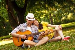 Potomstwo para w miłości bawić się gitarę akustyczną fotografia stock