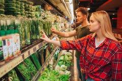 Potomstwo para w sklepie spożywczym Stoją przed ziele półką i podnoszą one wpólnie Poważni skoncentrowani ludzie wewnątrz zdjęcia royalty free