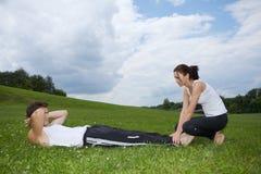 Potomstwo para ćwiczy w parku Zdjęcia Stock
