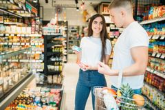 Potomstwo para wybiera produkty w supermarkecie obrazy stock
