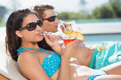 Potomstwo para z napojami pływackim basenem Zdjęcie Royalty Free