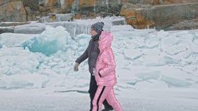 Potomstwo para zabawę podczas zima spaceru przeciw tłu lód zamarznięty jezioro Kochankowie chodzą na lodzie, trzymają each inny o zbiory