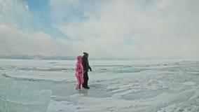 Potomstwo para zabawę podczas zima spaceru przeciw tłu lód zamarznięty jezioro Kochankowie chodzą na lodzie, trzymają each inny o zdjęcie wideo