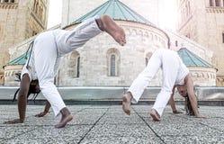 Potomstwo pary capoeira współpracuje spełniań kopnięcia plenerowych Obrazy Royalty Free
