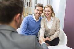 Potomstwo pary chwiania ręki agent nieruchomości w agencyjnym biurze Obraz Royalty Free