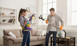 Potomstwo pary cleaning dom, bawić się z kwaczem fotografia royalty free