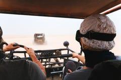 Potomstwo pary jeździecki zapluskwiony samochód w pustyni Obraz Royalty Free