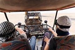 Potomstwo pary jeździecki zapluskwiony samochód w pustyni Zdjęcie Stock
