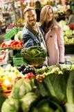Potomstwo pary kupienia warzywa na rynku Obraz Royalty Free