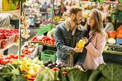 Potomstwo pary kupienia warzywa na rynku Obrazy Stock
