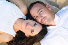 Potomstwo pary lying on the beach na kamiennej podłoga zdjęcia stock
