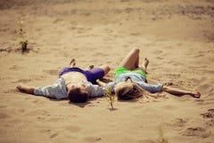 Potomstwo pary lying on the beach na piasku Obrazy Royalty Free