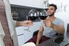 Potomstwo pary napoju wino W kuchni, Latynoskim mężczyzna I kobiety świętowaniu, Obrazy Stock