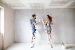 Potomstwo pary obrazu ściany w ich nowym domu Zdjęcia Stock
