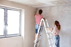 Potomstwo pary obrazu ściany w ich nowym domu Obrazy Stock