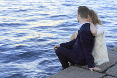 Potomstwo pary obsiadanie na nabrzeżu Zdjęcie Stock