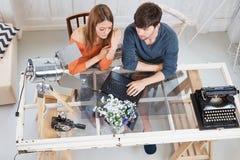 Potomstwo pary obsiadanie przy biurkiem w domu Zdjęcia Royalty Free