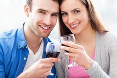Para wznosi toast z czerwonym winem Zdjęcia Royalty Free