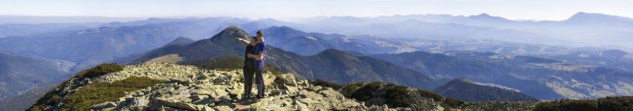 Potomstwo pary podwyżka w Karpackich górach Mężczyzna i kobiety pozycja na halnym odgórnym patrzeje pięknym krajobrazie below Sze Obrazy Stock