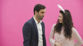 Potomstwo pary pozycja na różowym tle Żona różowy królik na jej głowie, trzyma w jej ręka królika ucho i zbiory wideo