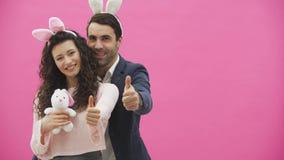 Potomstwo pary pozycja na różowym tle Podczas ten przedstawienia gest klasa uśmiecha się miękką zabawkę w rękach i trzyma zdjęcie wideo