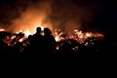 Potomstwo pary sylwetka - patrzeć ogienia Fotografia Royalty Free