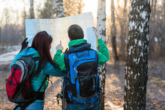Potomstwo pary wycieczkowicze patrzeje mapę Fotografia Royalty Free