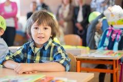 Potomstwo pierwszy stopnia studencki obsiadanie przy biurkiem na jego pierwszy dniu przy sc Fotografia Stock
