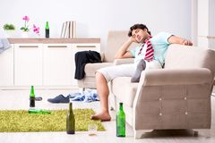 Potomstwo pijący przystojny mężczyzna po przyjęcia w domu fotografia stock