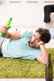 Potomstwo pijący przystojny mężczyzna po przyjęcia w domu obraz stock