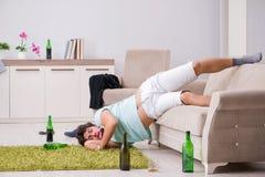 Potomstwo pijący przystojny mężczyzna po przyjęcia w domu fotografia royalty free