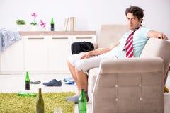 Potomstwo pijący przystojny mężczyzna po przyjęcia w domu obrazy stock