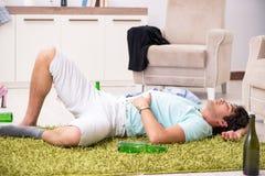 Potomstwo pijący przystojny mężczyzna po przyjęcia w domu zdjęcia royalty free